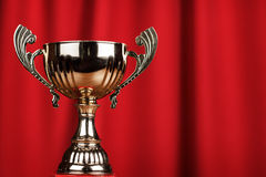 Golden trophy cup over red background Royalty Free Stock Image