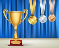 Golden trophy cup and set of medals with ribbons on blue curtain Royalty Free Stock Images