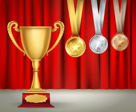 Golden trophy cup and set of medals with ribbons on red curtain Royalty Free Stock Images