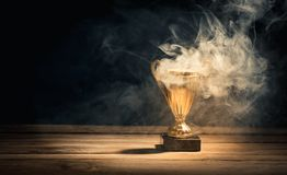 Golden trophy cup with smoke on table. Golden sports trophy cup on wood desk with dramatic strong contrast light and shadow, sports winner or leader achievement royalty free stock photo