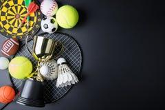 Golden Trophy, Darts, Racket Table Tennis, Ping Pong Ball, Shuttlecocks, Badminton Racket And Tennis Ball On Black Royalty Free Stock Image