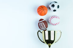 Golden trophy, Football toy, Baseball toy, Basketball toy and Ru. Gby toy on white background with copy space.Concept winner of the sport royalty free stock photo