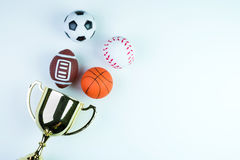 Golden trophy, Football toy, Baseball toy, Basketball toy and Ru. Gby toy on white background with copy space.Concept winner of the sport stock photo