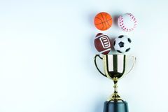 Golden trophy, Football toy, Baseball toy, Basketball toy and Ru. Gby toy on white background with copy space.Concept winner of the sport royalty free stock images