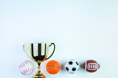 Golden trophy, Football toy, Baseball toy, Basketball toy and Ru. Gby toy on white background with copy space.Concept winner of the sport stock image
