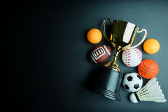 Golden trophy, Football toy, Baseball toy, Ping pong ball, Shuttlecock, Basketball toy and Rugby toy isolated on black background. Golden trophy, Football toy stock photography