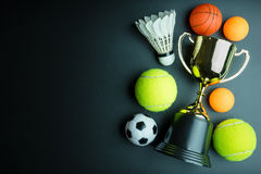 Golden trophy, Football toy, Baseball toy, Ping pong ball, Shuttlecock and Tennis isolated on black background with copy. Golden trophy, Football toy, Baseball stock photo