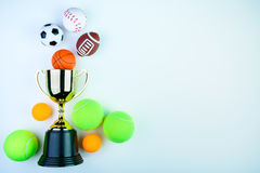 Golden trophy, Football toy, Baseball toy, Ping pong ball, Tennis ball, Basketball toy and Rugby toy isolated on white background. Golden trophy, Football toy royalty free stock photo
