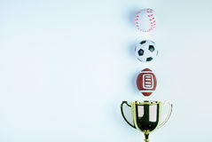Golden trophy, Football toy, Baseball toy and Rugby toy. On white background with copy space.Concept winner of the sport royalty free stock photo