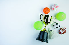Golden trophy, Football toy, Baseball toy, Shuttlecock,Tennis ba. Ll, Basketball toy and Rugby toy on white background with copy space.Concept winner of the stock images