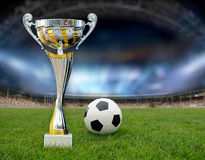Golden trophy. In grass on soccer field background stock photo
