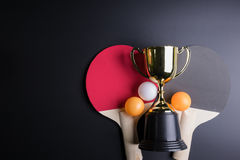 Golden trophy, Racket table tennis with ping pong ball on black Royalty Free Stock Photography