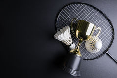 Golden trophy, Shuttlecocks and badminton racket on black background.Sport concept, Concept winner, Copy space image for your tex. T stock photo