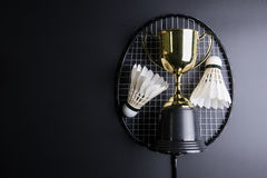 Golden trophy, Shuttlecocks and badminton racket on black background.Sport concept, Concept winner, Copy space image for your tex. T royalty free stock photography