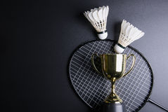 Golden trophy, Shuttlecocks and badminton racket on black background.Sport concept, Concept winner, Copy space image for your tex. T royalty free stock images