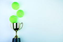 Golden trophy and Tennis ball on white background with. Copy space.Concept winner of the sport stock photography