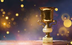 Golden trophy on wooden table, bokeh and glitter background with. Copy space royalty free stock photography