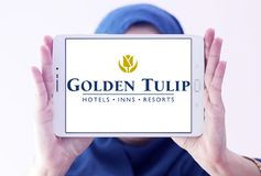 Golden Tulip hotels and resorts logo. Logo of Golden Tulip hotels and resorts on samsung tablet holded by arab muslim woman Royalty Free Stock Photos