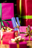Golden Twinkles, Bows and Gift Boxes. Six presents prepared for any gift-giving occasion. Focus is on the golden bow knot around the small magenta box on the Stock Photos