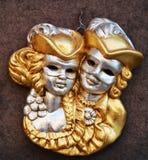 Golden Venetian lovers masks. Isolated golden Venetian lovers masks on the front shop, in Venice, Italy, Europe Stock Photo