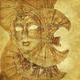 Golden Venetian mask on floral background. Rich golden Venetian Mask on floral grunge wallpaper with music sheets as decoration stock photography