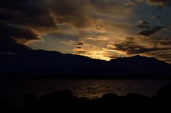 Golden vibrant sunset over snowy mountain and fjord Royalty Free Stock Image