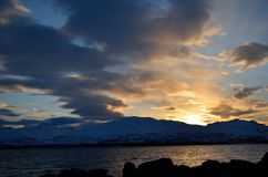 Golden vibrant sunset over snowy mountain and fjord Stock Photos
