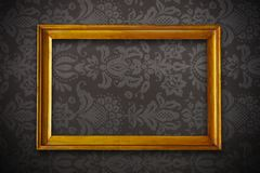 Golden vintage empty frame on floral wallpaper Royalty Free Stock Image