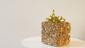 Golden vintage gift box revolves on a stand against a white wooden wall. 4k video.  stock video