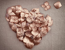 Golden vintage hydrangea  flower petals  in the shape of a heart. On fabric background Stock Image