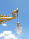 Golden Vintage Lamp with blue sky background (The King of Nagas). Golden Vintage Lamp with blue sky background (The King of Nagas in Thai temple Stock Photo