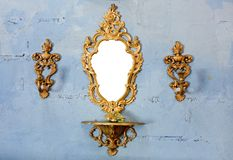 Golden vintage mirror with gold candlestick on wall. Closeup decoration design of Golden vintage mirror with gold candlestick on wall royalty free stock photography