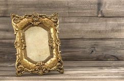 Golden vintage picture frame on wooden background Royalty Free Stock Photography