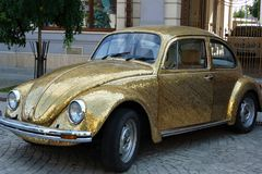 An original elegant golden vintage Volkswagen beetle car on cobblestone street stock photography