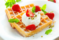 Golden waffle with strawberries and cream royalty free stock photography