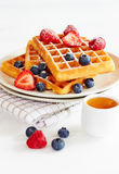 Golden waffles with berries and cup of honey Stock Photo