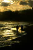 Golden Walk on Kauai. Couple walk down lonely beach at sunset on island of Kauai.  man is on the left.  Sunset is reflected on the waves washing ashore Royalty Free Stock Images