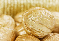 Golden walnuts against bokeh, finance or money concept Royalty Free Stock Photography