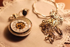 Golden watch. Golden vintage watch and some gold jewelery royalty free stock image