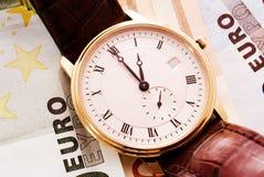 Golden watch on Euro banknotes Stock Photos