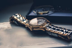 Golden watch. Laying flat on a wooden board Royalty Free Stock Photo