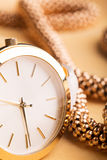 Golden watch and necklace Royalty Free Stock Image