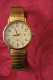 Golden watch on red cloth Royalty Free Stock Image