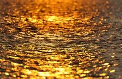 Golden water. A golden sea as background Stock Photos