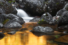 Golden Waterfall. The Macieira river in Peneda-Gerês National Park (northern Portugal) flows into a golden pool Stock Images