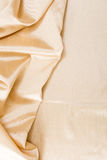 Golden wavy fabric background. Royalty Free Stock Photos
