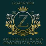 Golden wavy patterned letters and numbers with initial monogram in coat of arms form. Elegant font and elements kit for logo. Design Royalty Free Stock Photo
