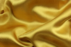 Golden wavy silk fabric Stock Images