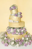 Golden Wedding Cake with White and Purple Roses Royalty Free Stock Photos