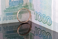 Golden wedding ring on the background of banknotes thousand rubles Stock Photos